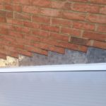 new roof next to red brick wall